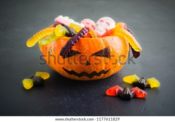 Natural pumpkin Jack with Halloween different candies on black background