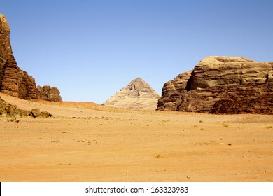 Natural Pyramid amid Desert Landscape with Rock Formations and Blue Sky, Wadi Rum, Jordan