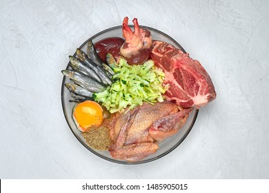 Natural raw dog food BARF diet in bowl Meat bone organs fish poultry egg vegetables organic food supplement