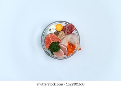 Natural raw dog food in bowl on white background. BARF Diet. Meat salmon egg yoghurt vegetables bones. Organic food supplement
