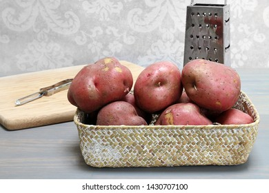 Natural, raw red potatoes in a basket ready to be prepared with utensils in background.