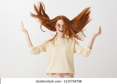 Natural redhead feeling happy. Studio shot of good-looking trendy ginger girl playing with hair, raising it up and standing with spread hands and broad smile in stylish sunglasses over gray wall