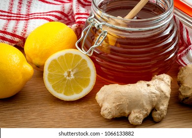 Natural remedies for cold and flu symptoms,  health and immunity boost and alternative medicine concept with close up on a jar of honey, lemon and ginger root in a wooden rustic kitchen table