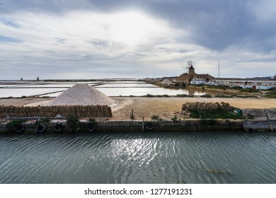 "Natural reserve ""Saline dello Stagnone"" with salt evaporation pond and the old windmill in the background, Marsala, Sicily, Italy"