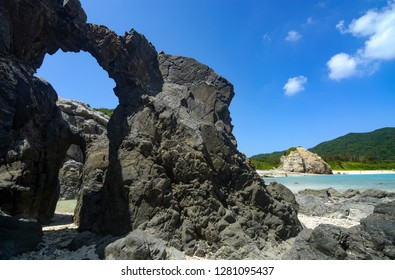 Natural rock arches along the coast at Aharen Beach on Tokashiki Island in Okinawa, Japan
