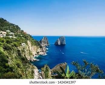 Natural rock arches and cliffs on the coast Sorrento and Capri, Italian islands with crystal clear waters where tourist boats crowd to photograph them in summer.