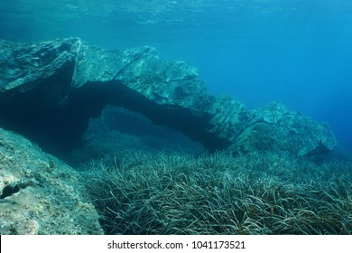 Natural rock formation underwater, an arch on the seabed with neptune grass in the Mediterranean sea, Catalonia, Cap de Creus, Costa Brava, Spain
