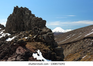 Natural rock wall with Mt Ngauruhoe in the background, as seen from Whakapapa ski field on Mt Ruapehu, New Zealand, in spring