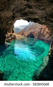 Natural rocky arch with crystal clear waters, in Tragonissi islet, Myconos, Greece