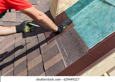 Natural roof tile installation. Roofer builder worker marks the distance between the seams