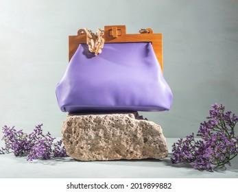 Podium naturel en pierre grise rugueuse avec sac à main femelle violet et fleurs. Concept minimal de shopping de mode d'été