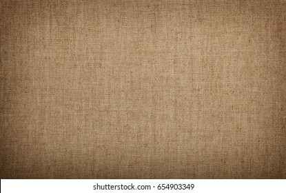 Natural rustic grey brown flax linen fabric textile sackcloth bagging canvas texture pattern background with darker border shade vignette