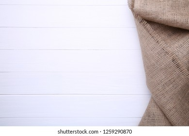 Natural sackcloth on white wooden background. Canvas on white wooden table