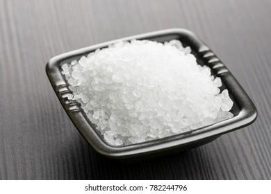 natural salt into black bowl on wooden table