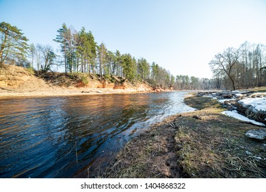 natural sand stone cliffs on the shore of the river in forest. Latvia