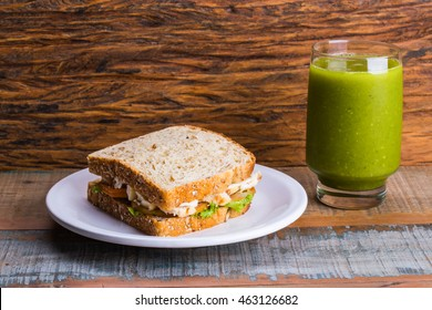 Natural Sandwich (Bread, cheese, tomatoes, chicken, onions, lettuce) and Green Juice (orange, cabbage, mint, ginger)/ Juice and sandwich/ Health Green Juice and healthy sandwich