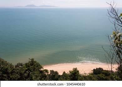 natural scenery of the blue sea from above the hill. there is a forest by the beach. there is an island in the background. blue sky in the evening.