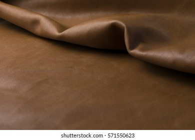 Natural seamless old vintage light brown leather texture background, folded original leather.
