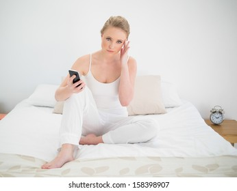 Natural serious blonde holding smartphone while sitting on bed in bright bedroom