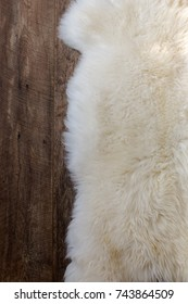Natural sheepskin fluffy fur rug on dark oak wooden floor. Vertical close up crop, top view