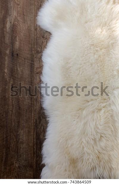 Natural sheepskin fluffy fur rug on dark oak wooden floor. Vertical close up crop, top view