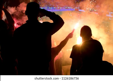 Natural silhouettes of football fans watching a match on the big street screen with fireworks in the night