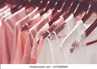 Natural silk colored and white, pink, coral nightgowns gowns hang in the store.Side view, soft focus, trend toning