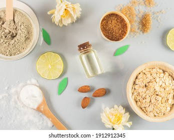 natural skin care products: honey, clay powder, brown sugar, almond oil, oats. Colorful background of natural cosmetics and flowers. natural ingredients for body scrubs on grey background