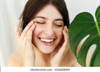 Natural Skin Care and Treatment. Portrait of beautiful young happy woman holding hands and massaging skin at green palm leaf. Girl enjoying effect after lifting anti-wrinkle patches under eyes