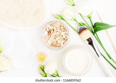 Natural skin cleansing product for body detox. Jar of oat flakes and cream top view, essential oils, flowers, white table, home spa.