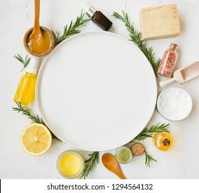 Naturkosmetische Produkte mit Ölen, Manuka-Honig, Zitrone, Rosmarin, Badesalz, Seife, Salbe mit Kopienraum rund weißer Platte in der Mitte
