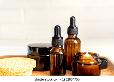 Natural skincare products in glass bottles. Serum and cream for facial skin. Herbal mineral cosmetic, vitamin body oil on wooden tray. Transparent package cosmetology with pipette for branding.