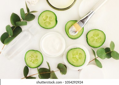 Natural skincare with refreshing green cucumber slices. Jar of cooling moisturizer with brush, eucalyptus leaves, top view. White and green colors.