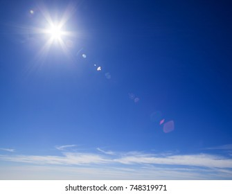 natural sky background with star-shaped sun and light clouds at the bottom, flare