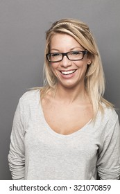 natural smile - sexy young blond woman with serious eyeglasses laughing expressing happiness and wellbeing,studio shot
