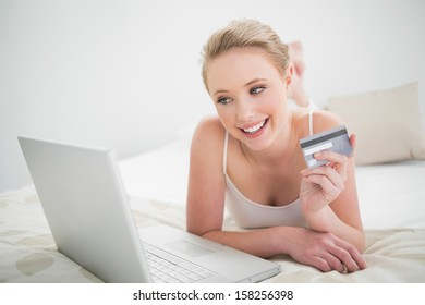 Natural smiling blonde holding credit card and looking at laptop in bright bedroom