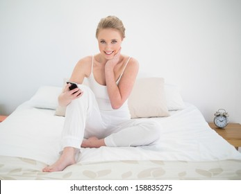 Natural smiling blonde holding smartphone while sitting on bed in bright bedroom
