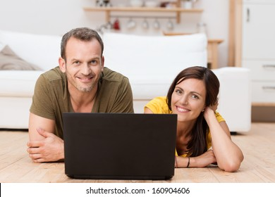 Natural smiling couple relaxing with a laptop lying together on the wooden floor in the living room enjoying a lazy day