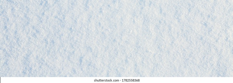 Natural snow texture. Smooth surface of clean fresh snow. Snowy ground. Winter background with snow patterns. Closeup top view. Wide panoramic texture for background and design.