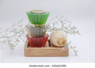 Natural soap with loofah. Natural Herbal Products. Melt and pour soap with natural loofah on wood soap dish with white background. close up.