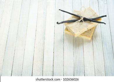 natural soap with vanilla beans on bright wooden background