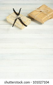 natural soap with vanilla beans and wrapped gift box, bright wooden background