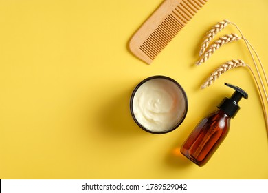 Natural SPA cosmetics set on yellow background. Flat lay amber glass pump bottle with shower gel, moisturizer cream for body, hair comb. Bathroom beauty products.