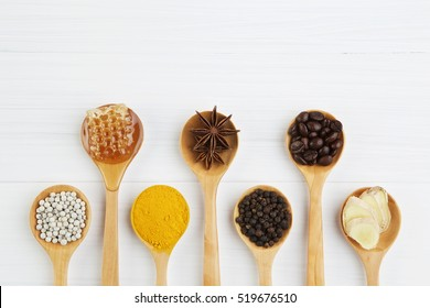 Natural Spa Ingredients. coffee beans, pepper, turmeric, ginger, honey, anise in wooden spoon. Variety herbs on white background from top view