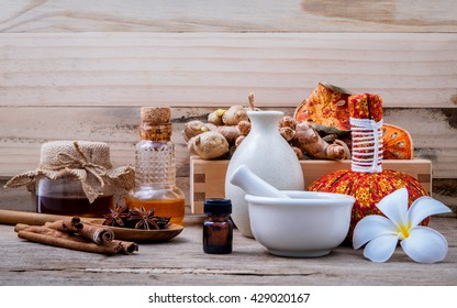 Natural Spa Ingredients herbal compress ball and herbal  Ingredients  for alternative medicine and relaxation Thai Spa theme with silk fabric on old wooden background.