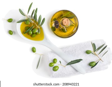 Natural spa setting with olives and olive oil, top view on white