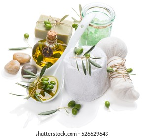Natural spa setting and treatment with olive oil, green olives, essential salt, herbal ball, zen stones and cotton towel isolated on white background.