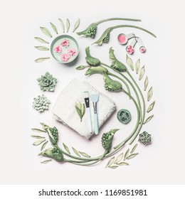 Natural spa and skin care composition with water bowl , flowers, green leaves, towel and accessories for facial mask on white background, top view. Healthy lifestyle and beauty concept