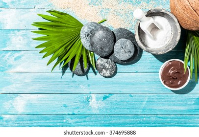 Natural spa therapy items as background with various sponges, sea salt, palm leaf and stones over blue wooden panels
