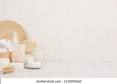 Natural spa white cosmetics products and beige bamboo rustic decor on white wood background, interior, border.